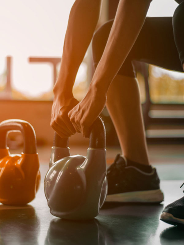 A woman lifts a kettlebell during her workout.