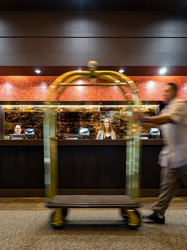 A bellhop moves through the hotel reception area.